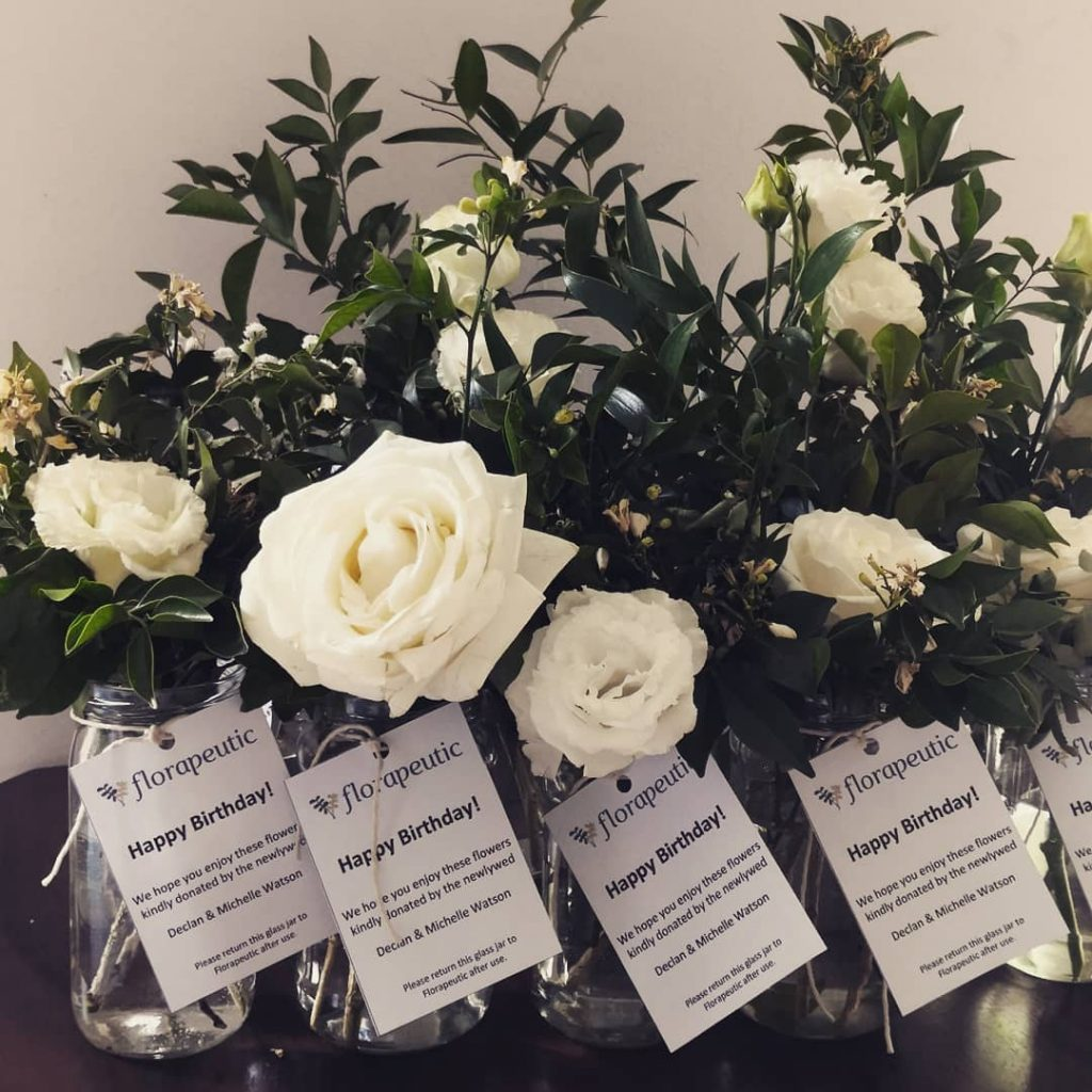 Donated white roses in glass jars with Happy Birthday tags